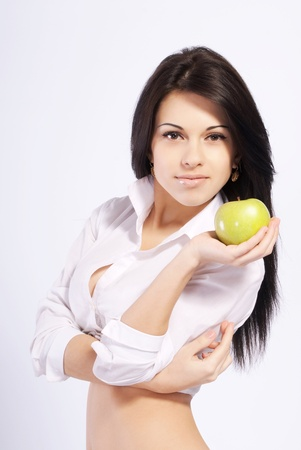 Naturally beautiful young girl in a blouse and skirt, holding an apple photo