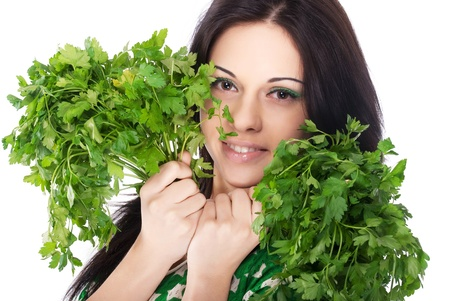 Young beautiful girl holding two bunches of parsley near the face Banco de Imagens