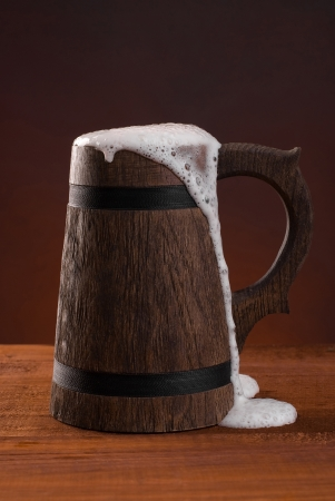 Wooden beer mug with beer and foam standing on a wooden table on a dark red background