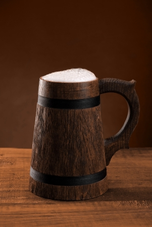 Mug of fresh beer with a cap of foam on a dark background  Stock Photo - 16434876