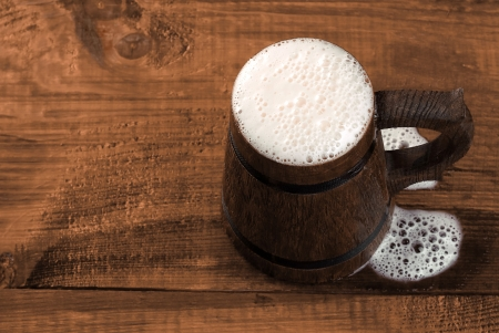 Full mug of fresh beer on a wooden table  View from above Stock Photo - 16434874