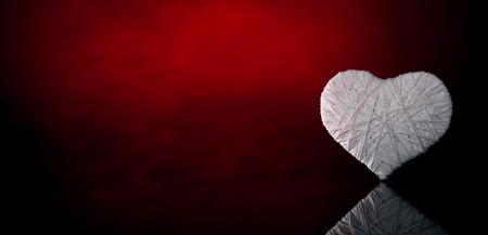 Wool white heart on a dark red background. Valentines Day.