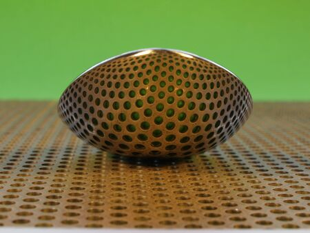 Spoon on perforated steel plate, reflecting the holes photo
