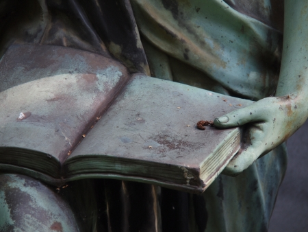 Detail of a grave stone statue holding a book photo