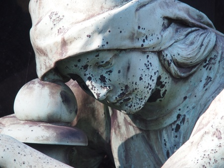 Detail of a gravestone showing the face of a sorrow woman photo