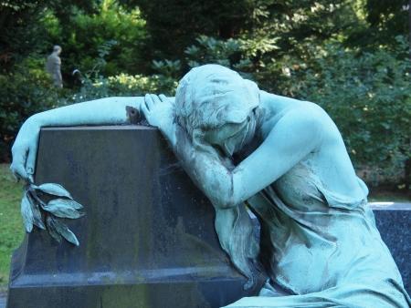 Standbeeld op een kerkhof leunen op een blok graniet Stockfoto