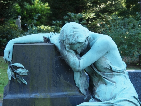 weeping angel: Statue on a graveyard lean on a block of granite