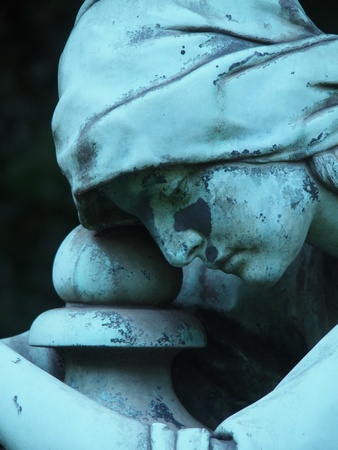 weeping angel: Detail of a gravestone statue showing the face of a sorrow woman