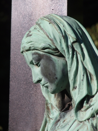 Detail of a gravestone showing the face of a sorrow woman
