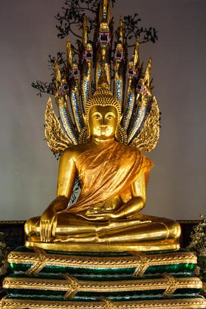 moksha: Golden sculpture of meditating Buddha and naga