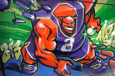 Colorful graffiti of monster playing basketball on the street