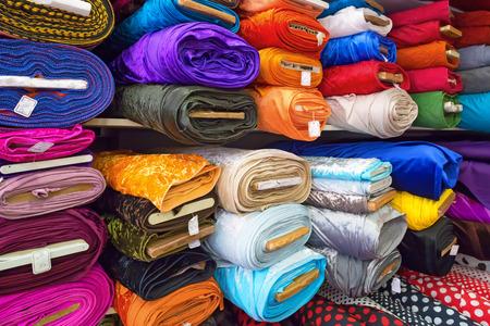 衣料品、布、市場に様々 な色の組織のロール