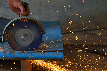sharpening process: A man is cutting metal with angle grinder Stock Photo