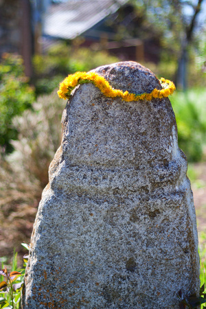 circlet: Pagan stone idol decorated with circlet of flowers