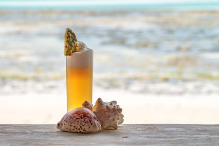 stillife: A glass of fresh tropical juice with sea shells and pineapple. Tropical stillife.
