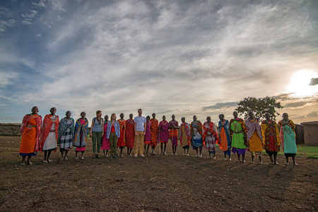 african warriors: MAASAI VILLAGE, KENYA - JANUARY 2 2015: Tourists visit maasai village near Maasai Mara. Watching traditions of local tribes is one of the most popular attraction for tourists who come to Kenya.