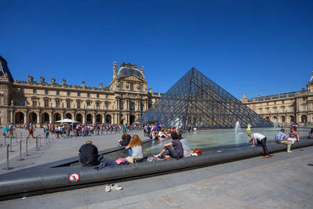 louvre pyramid: PARIS, FRANCE - CIRCA JUNE 2014: Tourists in the Louvres central courtyards with the Louvre pyramid and palace. The Louvre is the worlds most visited museum Editorial