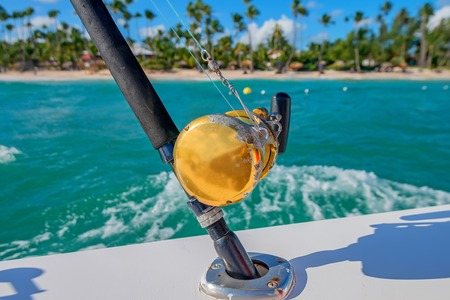 marlin: Boat fishing rods and closeup reel in front of tropical coastline