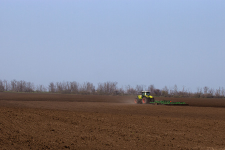 harrowing: Tractor does harrowing and cultivation of arable land preparing it  for sowing