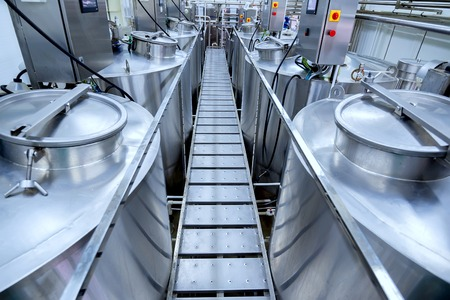 Equipment at modern dairy plant with stainless tanks