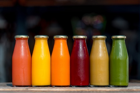 Variety of organic cold-pressed raw fruit and vegetable juices in glass bottles