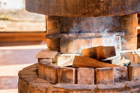 Firewoods burn in oven made of stone in traditional style Stock Photo