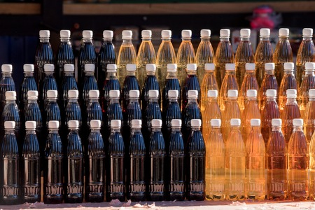 corked: Bottles of refreshing homemade juices at a traditional market on rustic red wooden stall