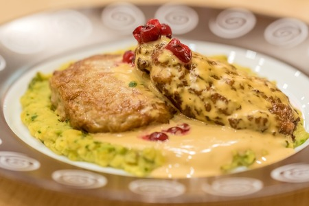 chese: Meat patties or frikadeller in chese and mushroom sauce decorated with berries Stock Photo