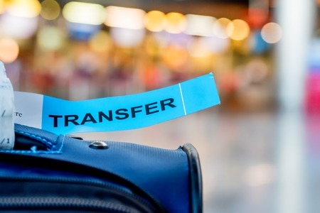 Close-up photograph of luggage with transfer label at airport with blurred background. Problems with transfer. Lost baggage Stock Photo