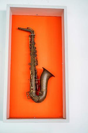 tenor: Retro saxophone on orange color wall background
