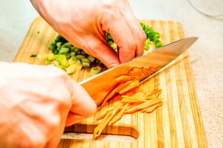 Female hand with knife cuts the carrot Stock Photo