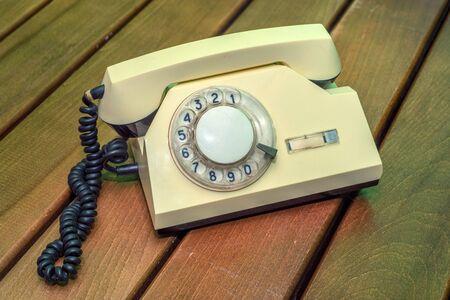 通信: Old beige disk phone on wooden background