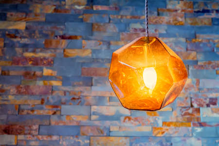 night table: Modern stylish orange lamp hangs from ceiling Stock Photo