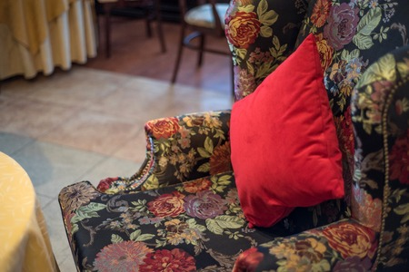 Red cushion on vintage armchair Stock Photo