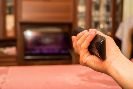 Hand holds TV remote control