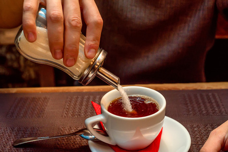 Hand puts sugar in cup with tea
