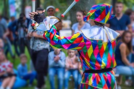 Back view streert juggler in bright clothing Foto de archivo