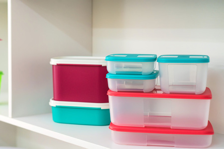 Group of modern plastic food containers on shelf Stock Photo