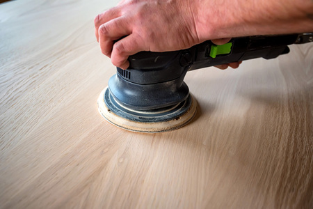 Man sanding wood with orbital sander in a workshop Reklamní fotografie
