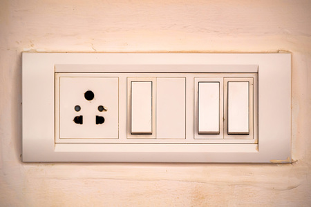 Beige rocker light switch with three buttons