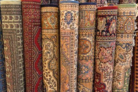 Colorful rolled carpets in oriental marketplace