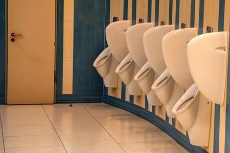 Close up row of urinals men public toilet