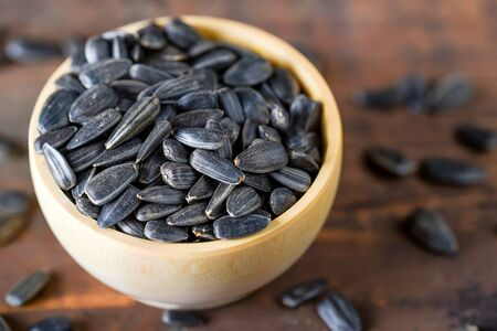 Unpeeled sunflower seeds in wooden bowl