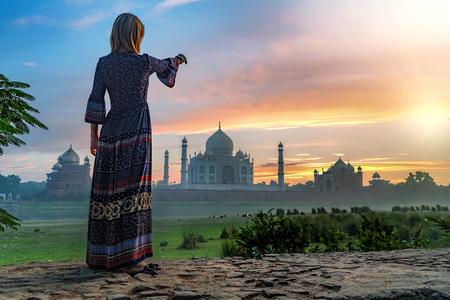 Beautiful girl points to Taj Mahal. Travel concept Stock Photo