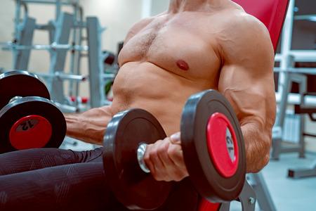 Männlicher Athlet, der Bizeps tut, trainieren mit Dummköpfen