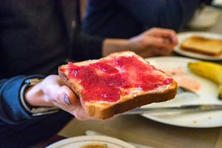 Hand holds a piece of bread with red jam Stock Photo