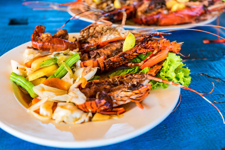 Tasty lobsters and jumbo prawns prepared with garlic and lime on tropical background. Traditional Lankan cuisine. Stock Photo