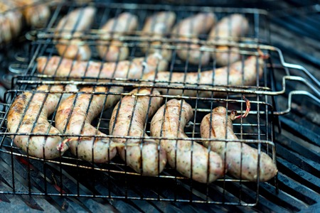 Cooking delicious German sausages on barbecue grill. Close up. Selective focus