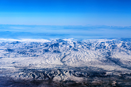 Scenic aerial landscape of lifeless mountains with snowy tops from airplane