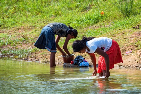 KANDY, SRI LANKA - CIRCA DECEMBER 2013: Unidentified Sri Lankan girls wash cloth